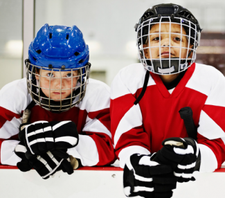 Two kids in hockey equipment